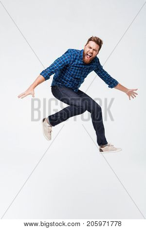 Full length portrait of a excited funny bearded man jumping isolated over white background