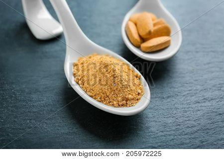Camu powder and pills in white ceramic spoons on dark background