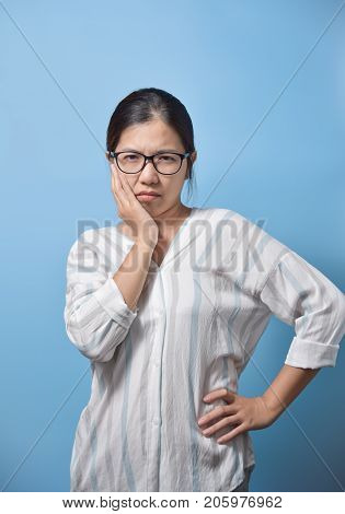 Toothache concept. Frustrated young Asian Glasses woman touching her cheek and standing on blue background. Copy space.