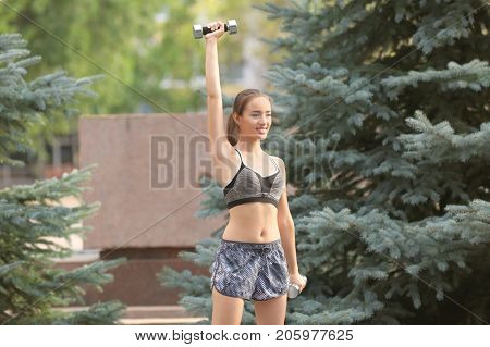 Young sporty woman doing exercise with dumb-bells in green park