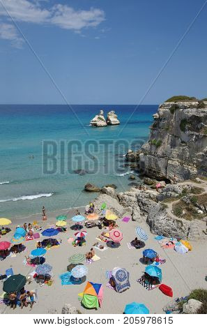 LECCE ITALY - JULY 26 2017: the crowded beautiful beach of Torre dell Orso with the Due Sorelle rocks