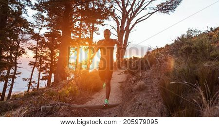 Focused young African man running down a trail in the forest while out for a cross country run in the late afternoon