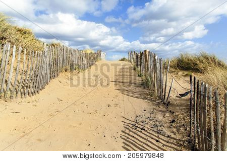 Path through the sand dunes onto a beach with fencing to stem the erosion and a blue sky background