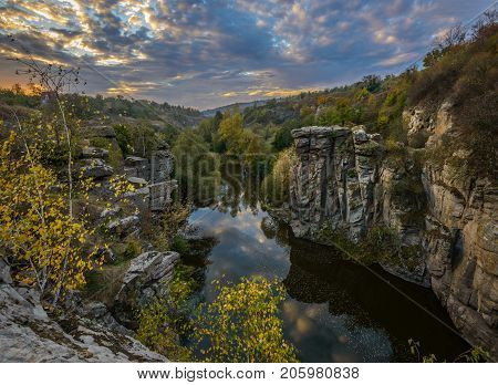 Canyon rocks are covered with autumn yellow trees. Sky with illuminated clous reflects in tranquil water. Buki canyon. Ukraine.