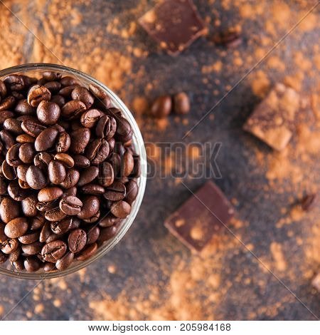 Close Up Part Of Full Glass Cup Of Roasted Coffee Beans On The Dark Stone Background With Dissipate