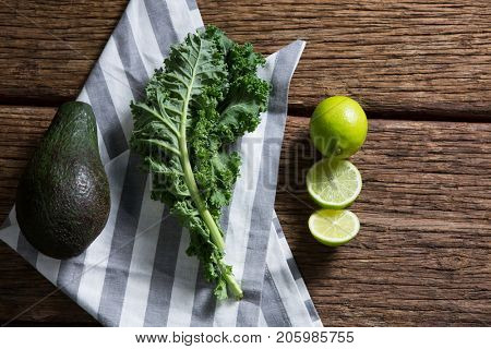 Overhead of mustard greens, avocado and lemon on wooden table