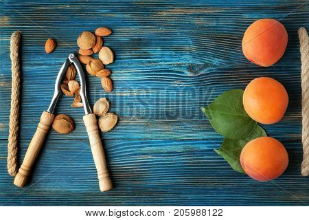 Nutcracker tool with apricots and kernels on wooden background