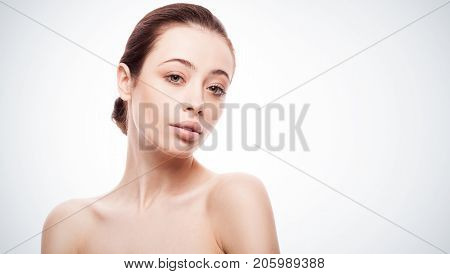 closeup portrait of young woman with clean fresh skin isolated on bue gradient studio background