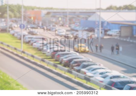 Abstract blurred view of row of cars on urban parking lot on sunny day, next to shopping center, outside. For background abstract