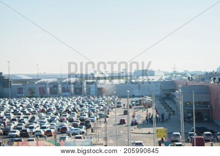 Blurred view of full parking lots next mall complex, outdoor. Uncovered crowded parking modern shopping center, bokeh light, retail store, for abstract background, copy space