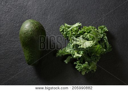 Overhead of avocado and mustard greens on black background