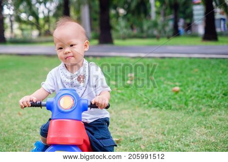 Cute little Asian 1 year old toddler baby boy child riding his tricycle in summer park kid playing toy and cycling in the garden outdoors Child first experience concept