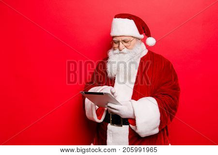Concentrated Saint Nicholas Looks At Emails From Children About Gifts On Pda Digital Device Screen M