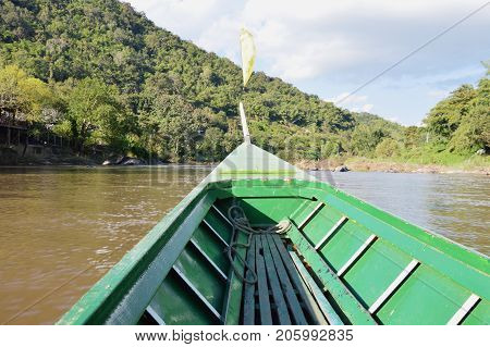 long tail motor boat sailing on river in sunny day