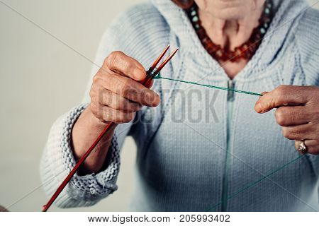 Hand made knitting. Unrecognizable lady wears a knitted sweater for the winter. Warm clothes. Manufacture of wearing apparel. Hobbies and pensions. Female hands knit wool