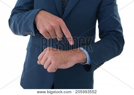 Mid section of businessman pointing on invisible wrist watch while standing against white background