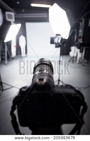 Professional camera set for a studio photo shoot. Focus on the camera lens.