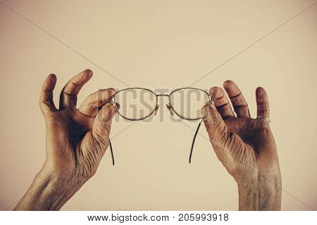 Old age glasses woman holding glasses for sight. Eyes with problems health and blurred vision with age. Old female hands hold glasses in beautiful frame for reading vintage frame. Age eye problems