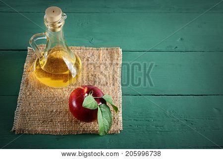 Red apples and apple cider vinegar on wooden table. Concept - healthy food from your garden. Top view. Copy space.