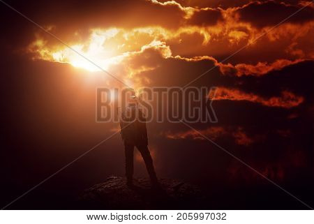 A mountain climber on a peak is silhouetted by an intense, fiery red sunset.