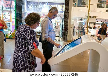SAINT PETERSBURG, RUSSIA - CIRCA AUGUST, 2017: man use information kiosk at Galeria shopping center. Galeria is major shopping and entertainment center is located in downtown of St. Petersburg
