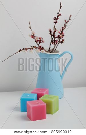 Bouquet of sprint blooming tree branches and few cubic candles
