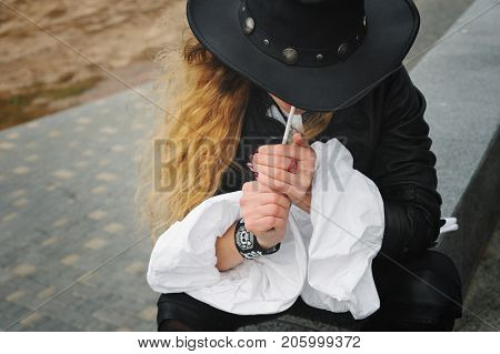 Fashion model smoking cigarette, leather jacket and hat, no face