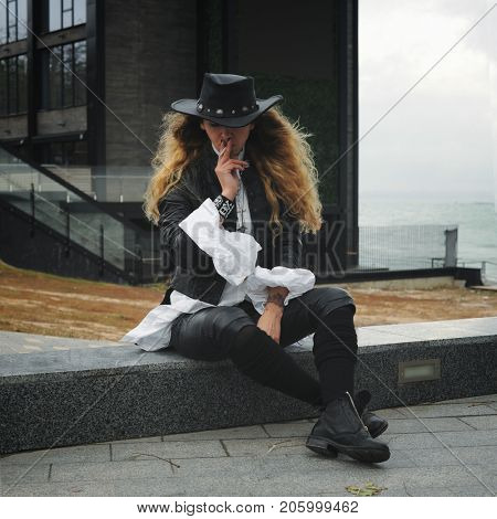 Fashion model portrait smoking cigarette, dressed in black leather jacket and hat