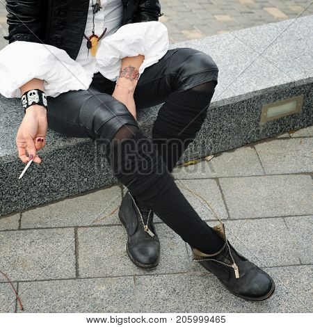 Fashion model hands holding cigarette, dressed in black leather jacket, white shirt and skull cow necklace