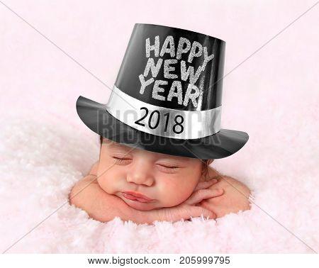 Newborn baby girl wearing a 2018 Happy New Year hat.