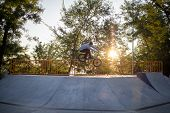 BMX rider training and do tricks in street plaza, bicyxle stunt rider in cocncrete skatepark poster