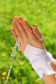 hands of the girl going to the First Holy Communion set in amen and praying with rosary against green grass background poster