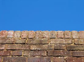 Brick Wall Against Blue Sky Background