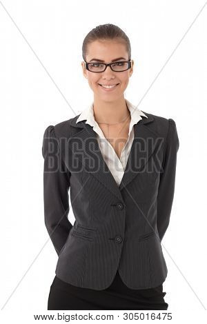 Portrait of young confident businesswoman wearing glasses, smiling at camera.