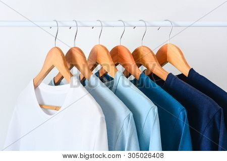 Close Up Collection Shade Of Blue Tone Color T-shirts Hanging On Wooden Clothes Hanger In Closet Or