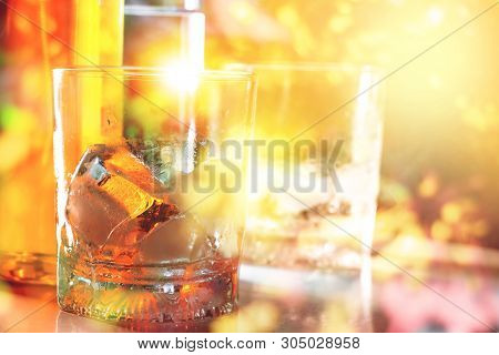 Glass Of Scotch Whiskey And Ice At Pub In Night Light