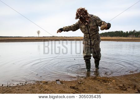 Duck Hunter Putting A Duck Decoy On The Shallow Water
