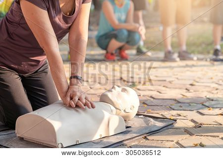 Candid Of Mature Asian Female Or Older Runner Woman Training On Cpr Demonstrating Class In Outdoor P
