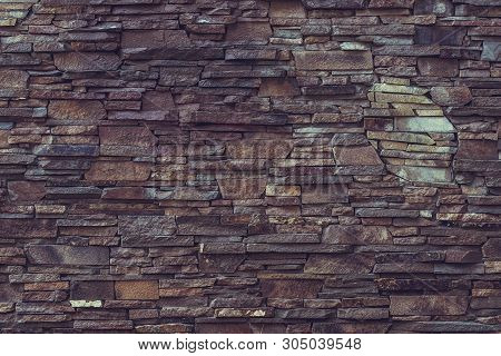 Old Brick Wall Background. Dark Brown Rough Stone Wall. Rock Wall Surface. Stony Texture. Grunge Mat