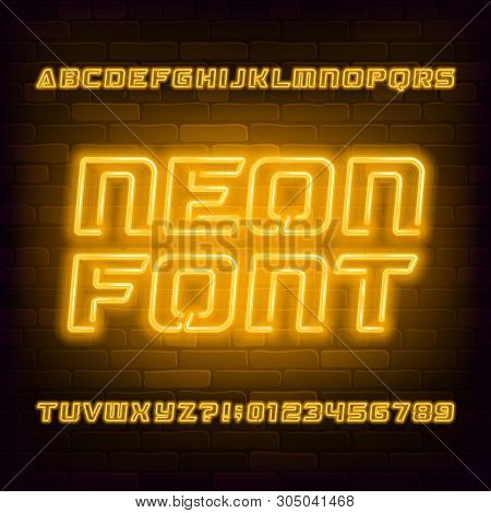 Yellow Neon Alphabet Font. Futuristic Light Bulb Capital Letters And Numbers. Brick Wall Background.