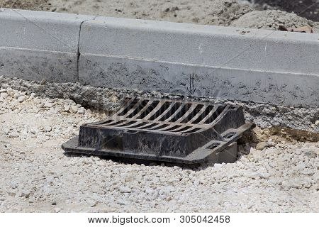 Metal rainwater gutter standing on gravel beside curbs at construction site poster