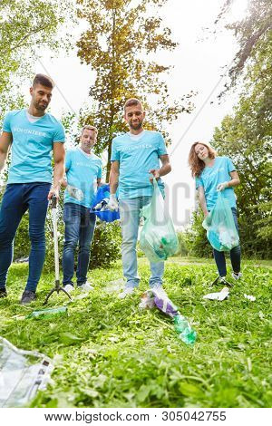 Group of volunteer environmentalists and volunteers collect garbage in nature