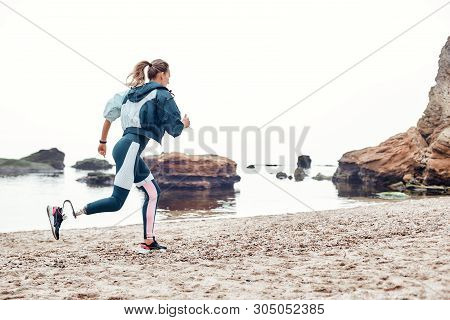 Take Care Of Your Body. Side View Of Strong Disabled Woman In Sportswear With Prosthetic Leg Is Runn