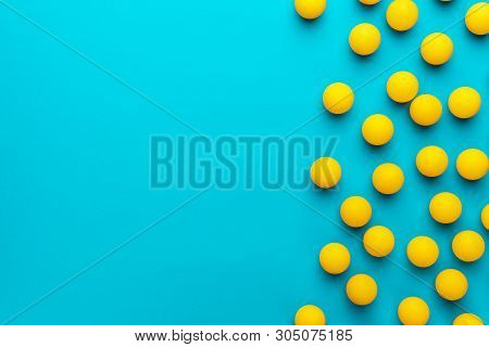 Many Balls For Table Tennis On Turquoise Blue Background. Flat Lay Image Of Many Yellow Table Tennis