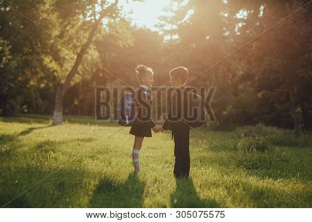 schoolchildren, little boy and little girl dressed in school uniform with schoolbag, holding hands, outdoor, at sunset poster