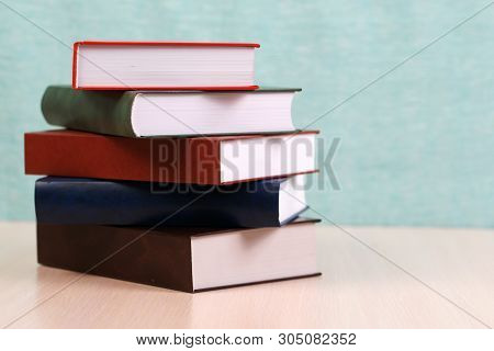 Open Book, Stack Of Hardback Books On Wooden Table.