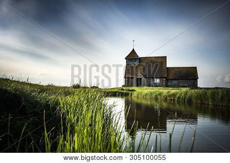 English Church Reflected In Waterway In Kent