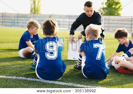 Football Coach Coaching Kids. Soccer Football Training Session For Young Boys. Young Coach Teaching