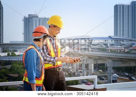 Man Engineers Stand On Tall Buildings And Talk About Cell Phones In The Field Of Construction. Engin
