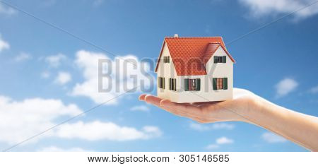 real estate, accommodation and property concept - close up of hand holding house or home model over blue sky and clouds background